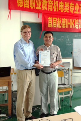 a German and a Chinese presenting a certificate