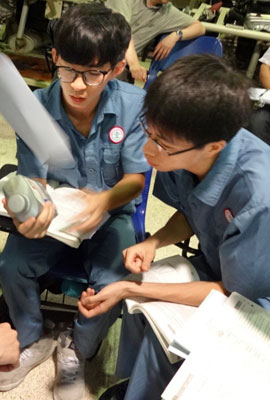 Two Chinese inspect a can