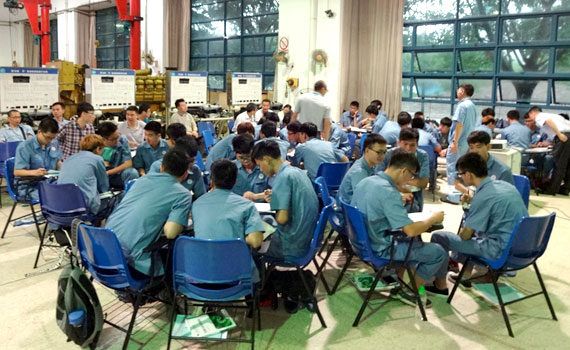 several chinese people sitting in small groups around tables and working together on something