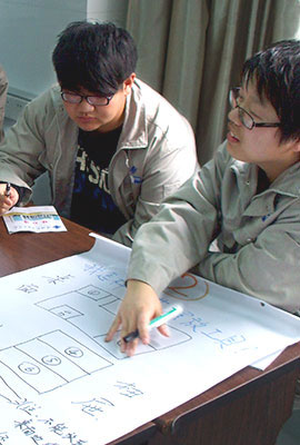 two chinese speaking about a poster