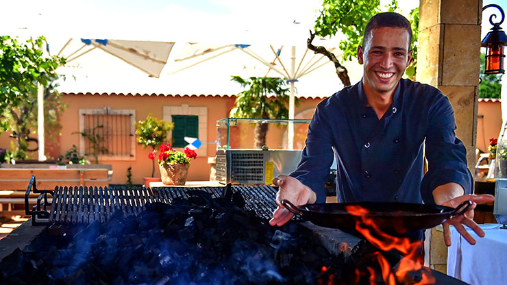 young man holds a pan over a grill fire and smiles into the camera