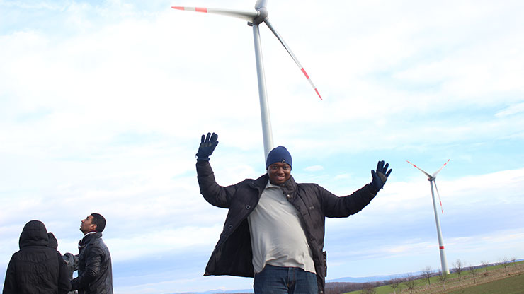 young African stands under windmills and waves into the camera
