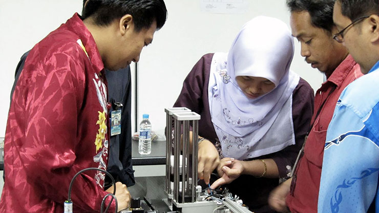 two men and a woman from Malaysia working in a workshop