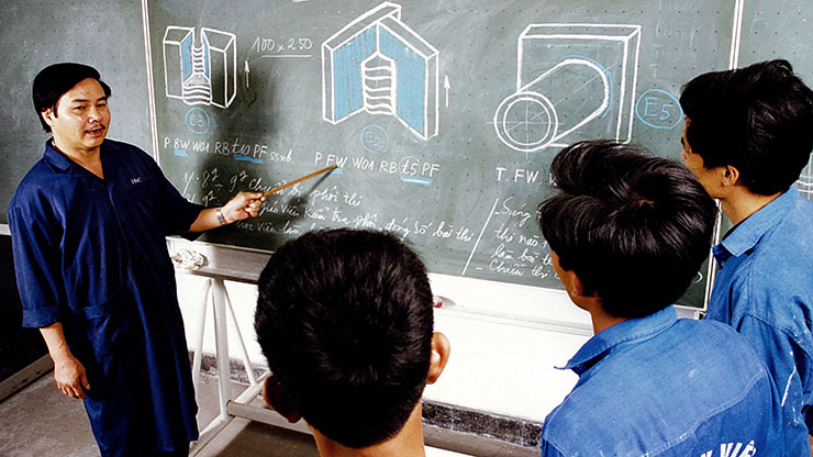 teacher explains various technical drawings to students on a blackboard