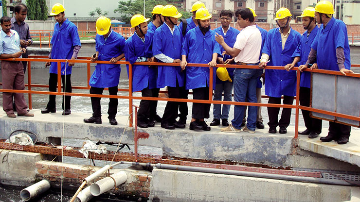 men in work clothes and protective helmets inspect a part of a sewage plant