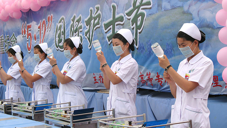 Chinese women in white coats stand in a row and draw syringes