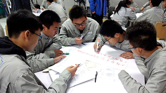 several chinese people sitting around a table preparing a poster