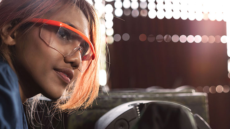 Woman with protective goggles looks past the camera