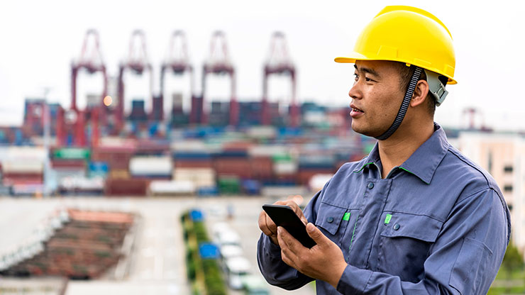 Asian man in work clothes typing on smartphone, cranes in the background