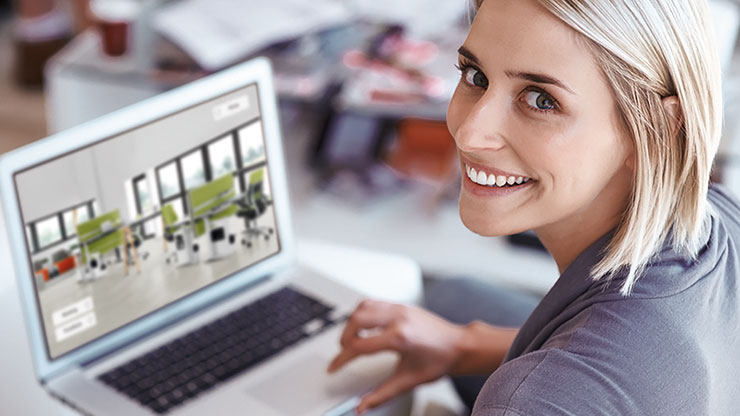 woman in front of a computer smiling into the camera