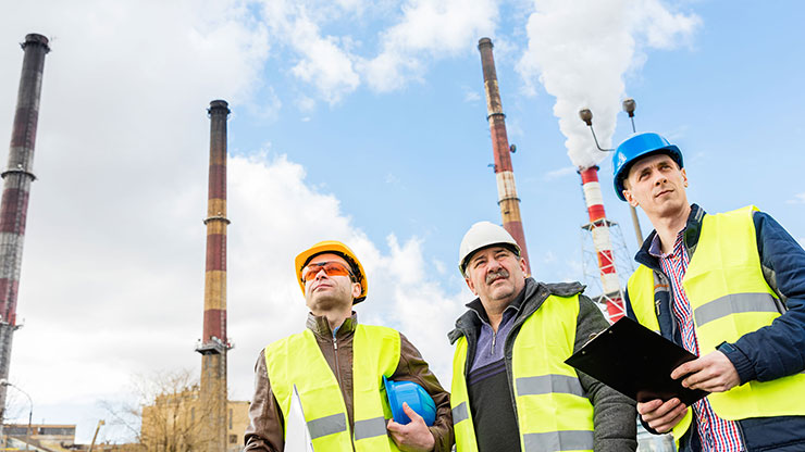 three men with safety vests and protective helmets stand in front of four chimneys