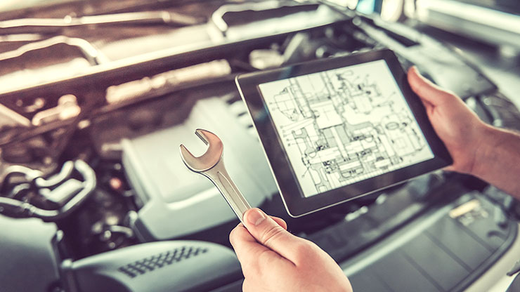 person holds tablet and wrench over a car engine